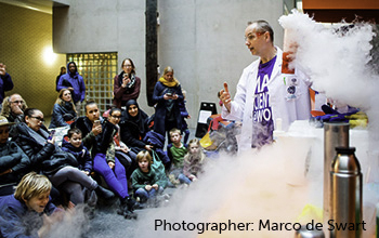 Mad scientist surrounded by smoke holding beaker with smoke pouring out.