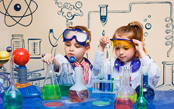 A boy and girl taking liquid from beaker using a pipette. On the table there are beakers and test tubes with colored liquids